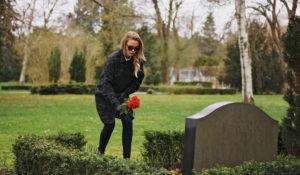お墓に花を添える女性
